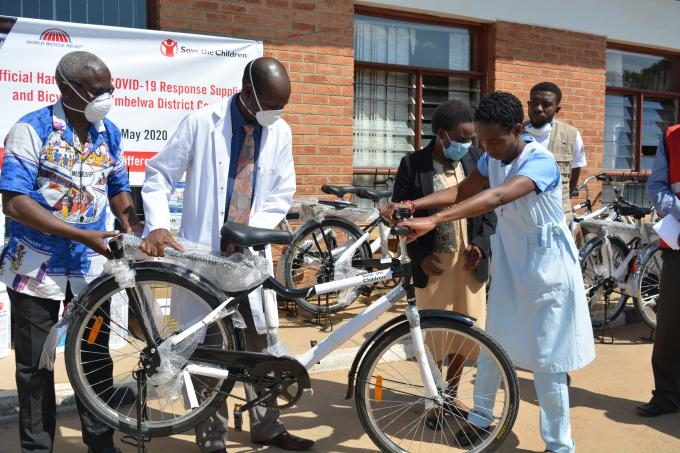 Official from Mbelwa council handing a bicyle to the beneficiary